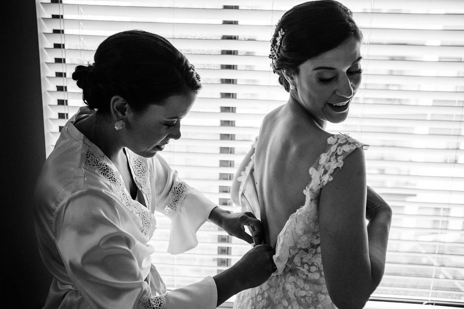sister helping the bride with dress