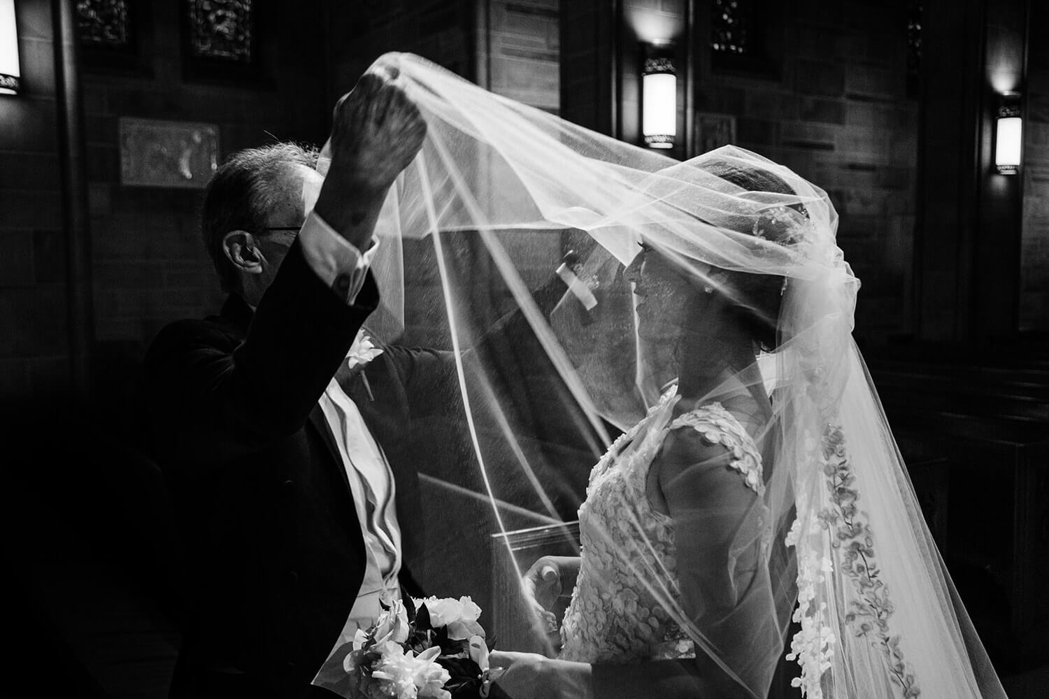 father helping the bride with the vel