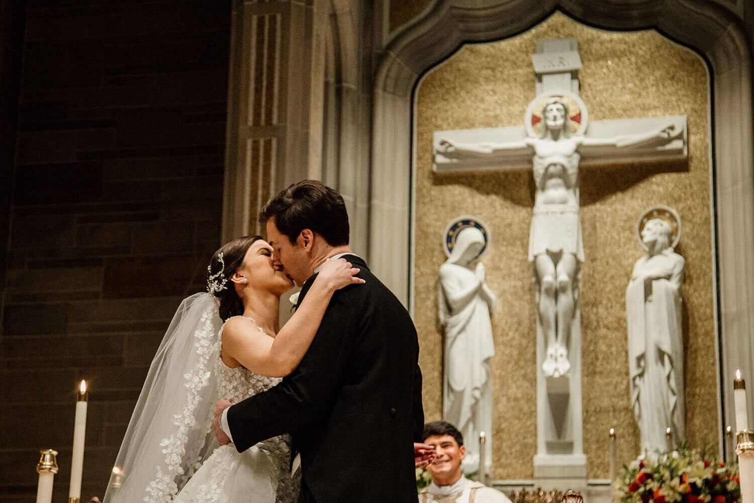 bride and groom kiss at the Cathedral of Christ the King