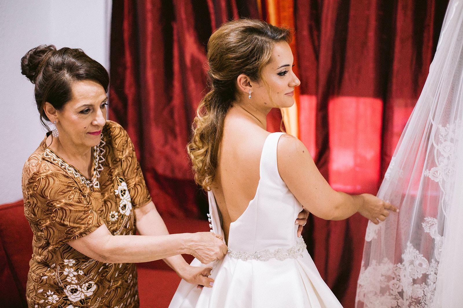 Madre vistiendo a su hija antes de la boda