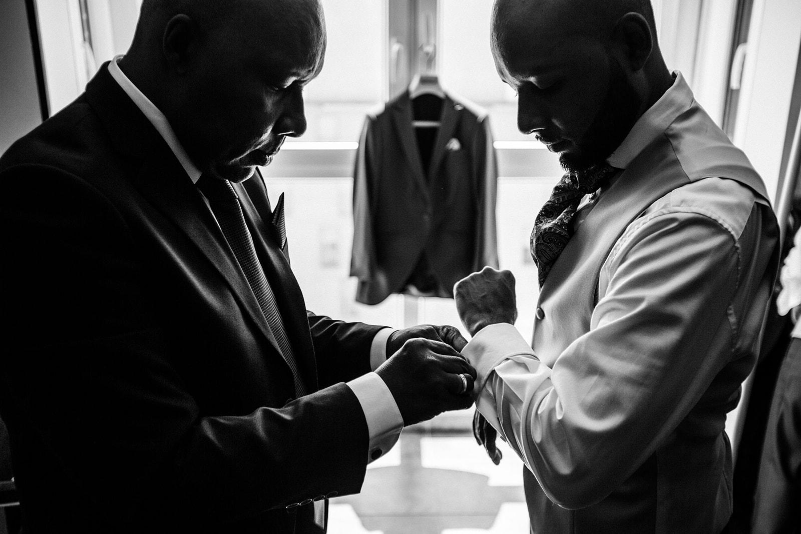 Padre ayudando a su hijo a vestir para la boda