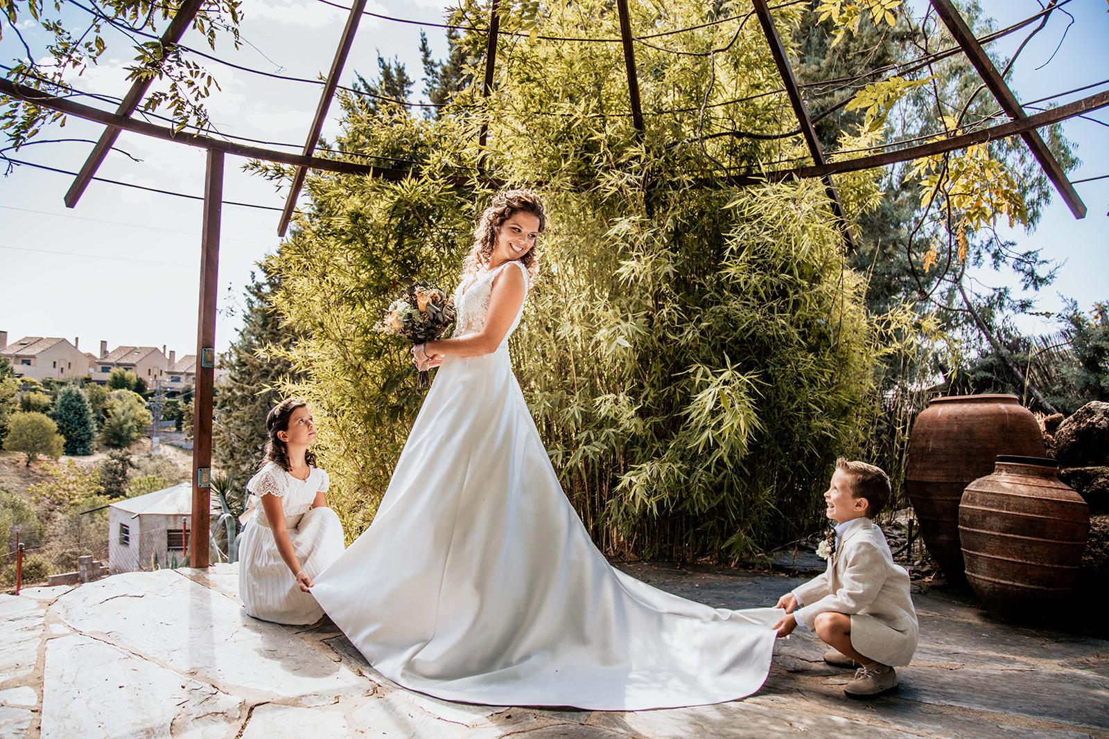 novia siendo ayudada por los pajesitos