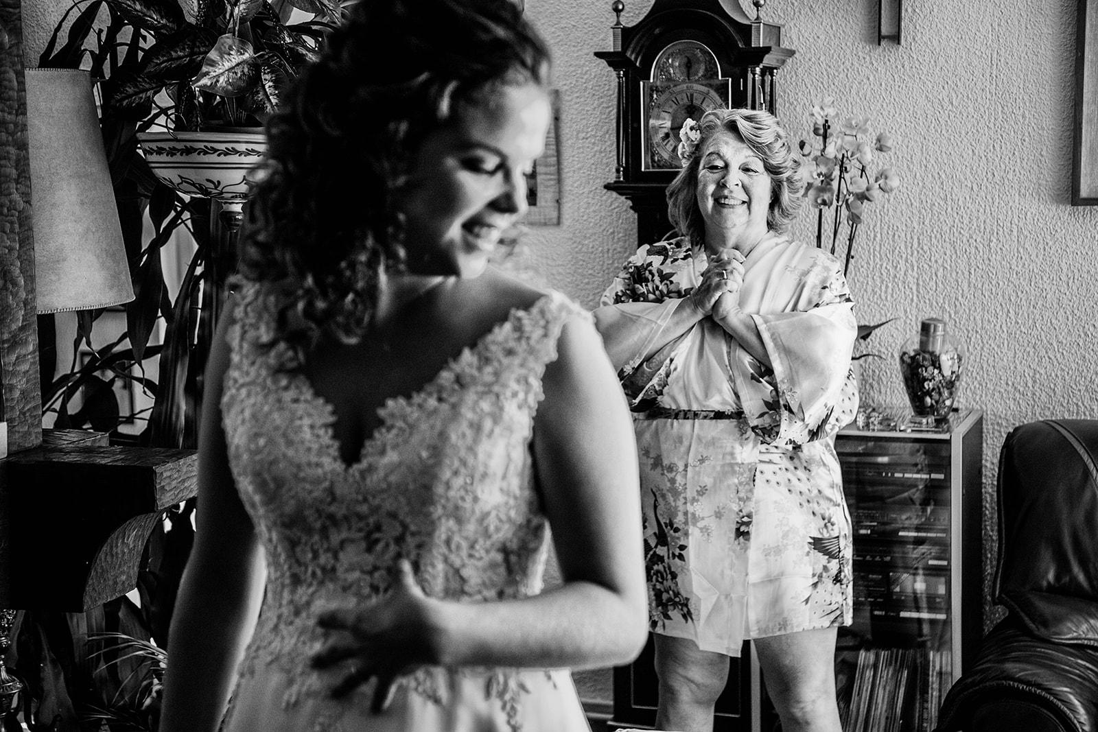 madre viendo su hija con vestido de novia