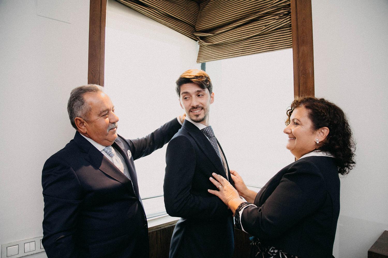 padres vistiendo a su hijo en la boda