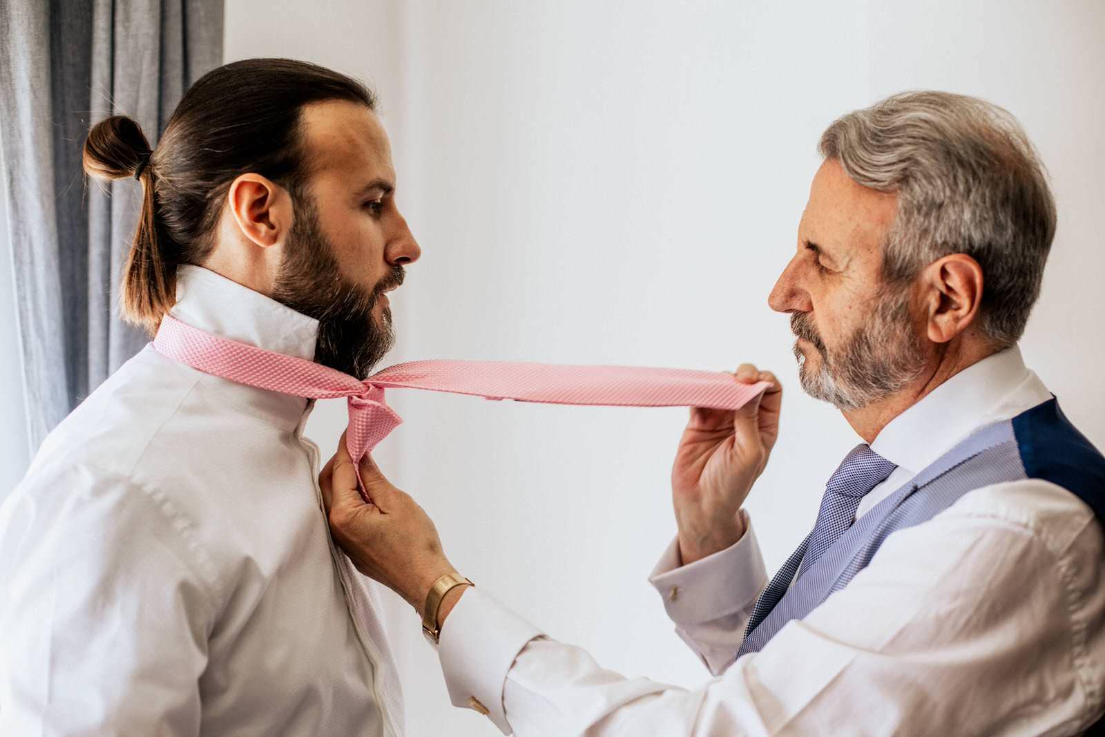 Padre ayudando a su hijo colocando la corbata en la boda